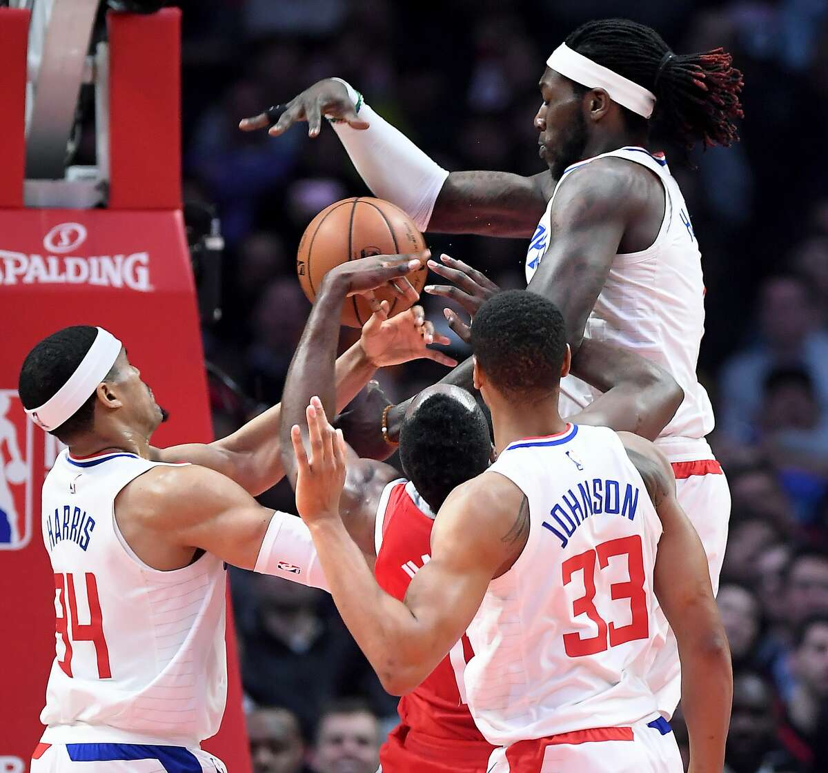 The Houston Rockets' James Harden is fouled by the Los Angeles Clippers' Wesley Johnson (33) as Tobias Harris, left, and Montezi Harrell help on defense in the first quarter at the Staples Center in Los Angeles on Wednesday, Feb. 28, 2018. (Wally Skalij/Los Angeles Times/TNS)