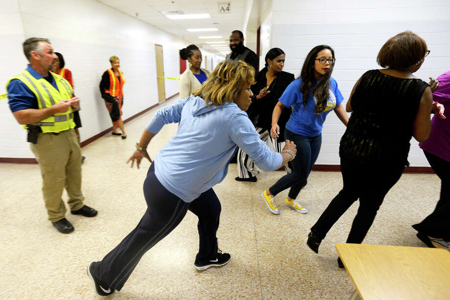 Participants scramble for an exit after hearing gunfire during an active shooter training session at Smith Middle School on Wednesday evening. Beaumont ISD and Beaumont Police Department provided the training to school administrators.  Photo taken Wednesday 2/28/18 Ryan Pelham/The Enterprise Photo: Ryan Pelham / ©2017 The Beaumont Enterprise/Ryan Pelham