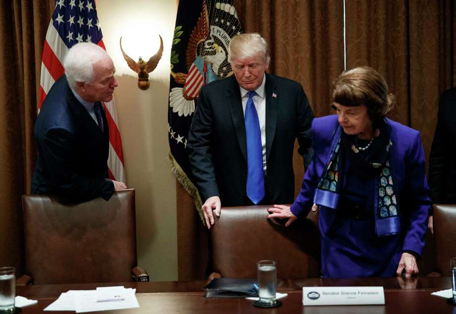 President Donald Trump pulls out a chair for Sen. Dianne Feinstein, D-Calif., right, as Sen. John Cornyn, R-Texas, talks at left, in the Cabinet Room of the White House, in Washington, Wednesday, Feb. 28, 2018, at the start of a meeting with the president and members of congress to discuss school and community safety. Photo: Carolyn Kaster, AP / Copyright 2018 The Associated Press. All rights reserved.