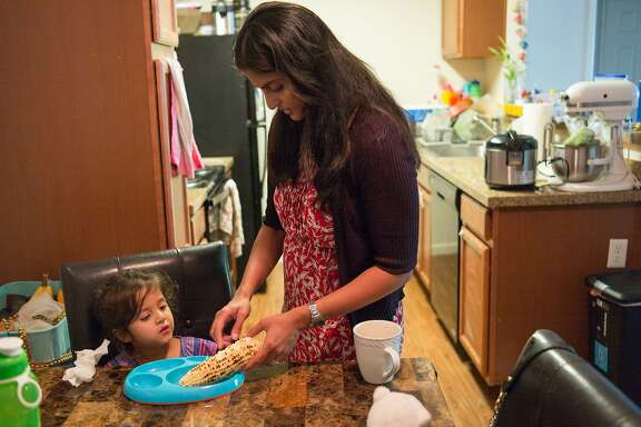 Karishma Chawla makes corn on the cob for her daughter Naisha at her home in San Jose, Calif. on Friday, Aug. 18, 2017. For decades spouses of H-1B visa holders could not work, until two years ago when President Obama issued a work authorization. But now his authorization is under threat by the Trump administration who is trying to rid these visa holders from the ability to work.