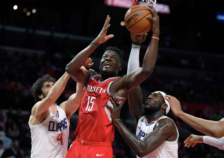 Houston Rockets center Clint Capela, center, of Switzerland, shoots as Los Angeles Clippers guard Milos Teodosic, left, and forward Montrezl Harrell defend during the second half of an NBA basketball game Wednesday, Feb. 28, 2018, in Los Angeles. The Rockets won 105-92. (AP Photo/Mark J. Terrill) Photo: Mark J. Terrill, Associated Press / Copyright 2018 The Associated Press. All rights reserved.