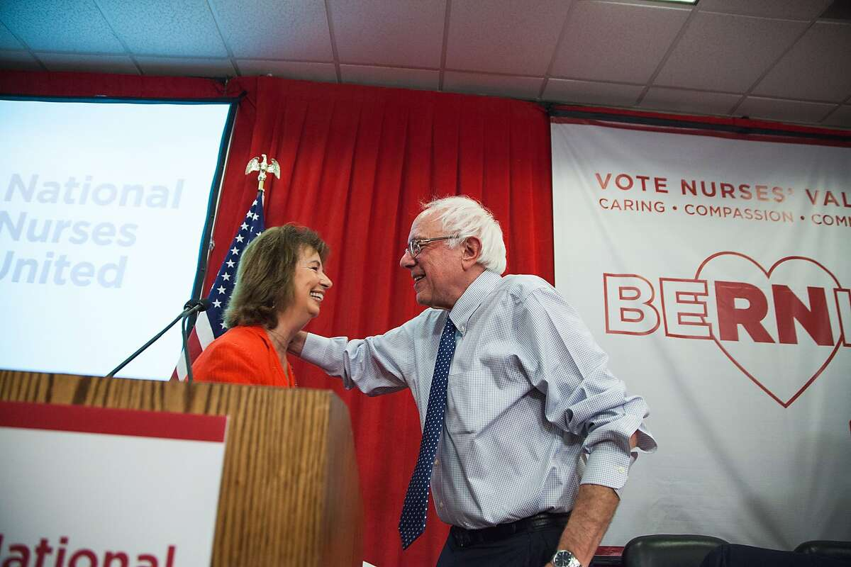 """National Nurses United executive director RoseAnn Demoro hugs Vermont Sen. Bernie Sanders on Monday, Aug. 10, 2015, at NNU's headquarters in Oakland, California. NNU, the nation?'s largest organization of nurses, hosted a ?""""Brunch with Bernie"""" where nurses throughout the nation joined by phone and in person to speak with Sanders."""