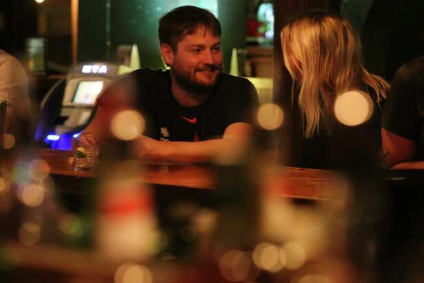Will Shropshire and Nicole Witt have a conversation at the bar on The Harp's closing night on Wednesday, Feb. 28, 2018, in Houston.