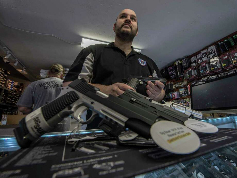 Craig Sarafini, owner of Upstate Guns and Ammo, displays handguns at his        store on Thursday, March 1, 2018, in Schenectady, N.Y.   (Skip        Dickstein/Times Union) Photo: SKIP DICKSTEIN, Albany Times Union / 20044107A