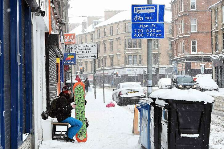 A man sips a coffee in full snowboard gear in Glasgow after snow covered the city on March 1, 2018.   Fresh heavy snowfalls and icy blizzards were expected to lash Europe Thursday as the region shivers in a deadly deep-freeze that has gripped countries from the far north to the Mediterranean south.     / AFP PHOTO / Andy BuchananANDY BUCHANAN/AFP/Getty Images