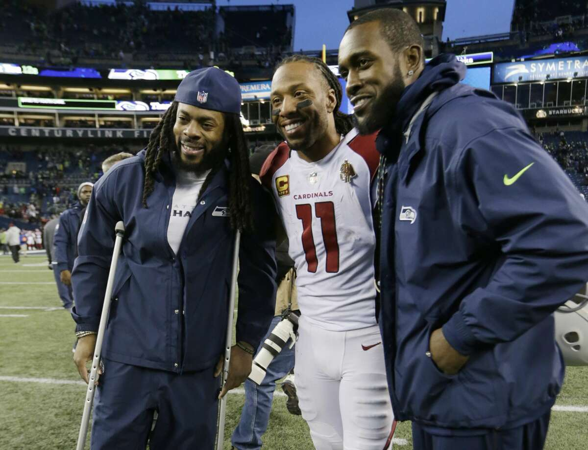 Arizona Cardinals wide receiver Larry Fitzgerald (11) poses for a photo with injured Seattle Seahawks' Richard Sherman, left, and Kam Chancellor, right, following an NFL football game, Sunday, Dec. 31, 2017, in Seattle. (AP Photo/John Froschauer)