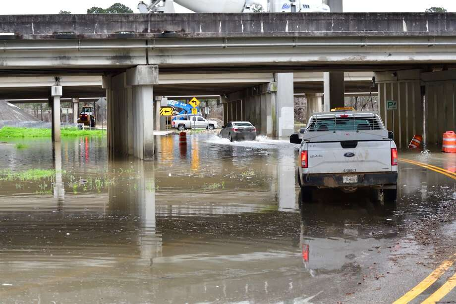 Cars drive through water standing under Interstate 69 in Kingwood after the San Jacinto River spilled out of its banks from a relatively moderate rainstorm on Feb. 26. Photo: Bob Rehak