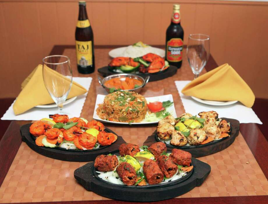 Offerings from Baingan Indian restaurant in Shelton, Conn.  Sunday, May 4, 2014. Dishes from front to back - Seekh Kabab, Shrimp Tandoori, left, Reshmi Kabab, Vegetable Biryani, Chicken Tikka Masala, Chicken Tandoori, Basmati Rice, and Indian Beer. Photo: BK Angeletti / B.K. Angeletti / Connecticut Post freelance B.K. Angeletti