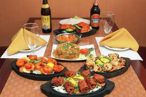 Offerings from Baingan Indian restaurant in Shelton, Conn.  Sunday, May 4, 2014. Dishes from front to back - Seekh Kabab, Shrimp Tandoori, left, Reshmi Kabab, Vegetable Biryani, Chicken Tikka Masala, Chicken Tandoori, Basmati Rice, and Indian Beer.