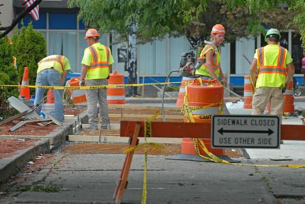 Construction workers fix the road at the corner of delaware avenue and