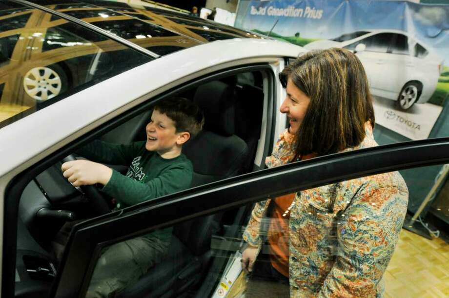Seven-year-old Jonathan Picchione grabs the wheel of a Toyota Prius hybrid on display as he and his mom Nancy Picchione of Albany tour the EcoShow at the Empire State Plaza in  Albany. (Michael P. Farrell/Albany Times Union) Photo: MICHAEL P. FARRELL