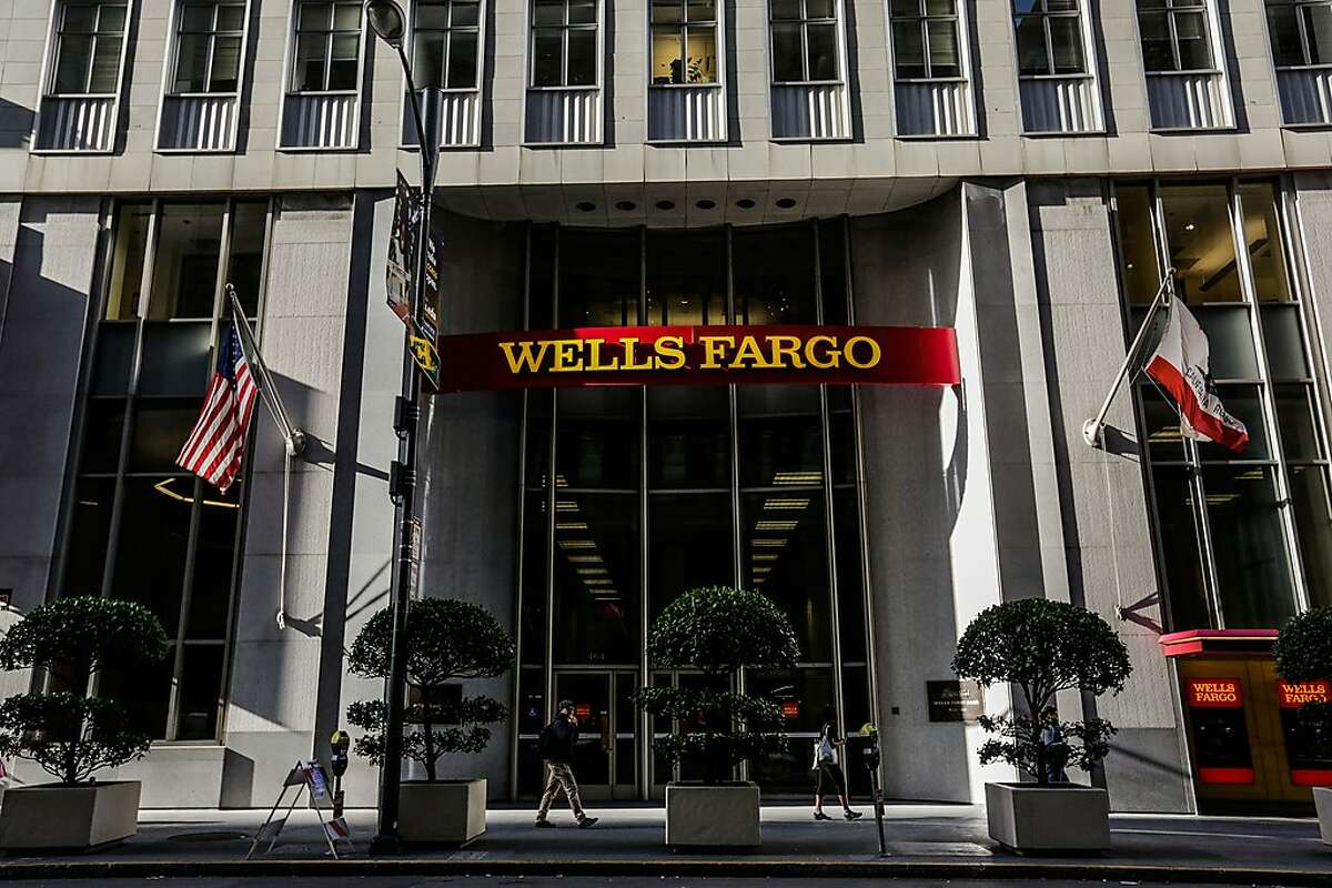 FILE-- People walk past a Wells Fargo bank on California Street in downtown San Francisco on Thursday, Sept. 14, 2017. Wells Fargo agreed Wednesday to pay a $2.1 billion fine to settle allegations it misrepresented the types of mortgages it sold to investors during the housing bubble that ultimately led to the 2008 financial crisis.