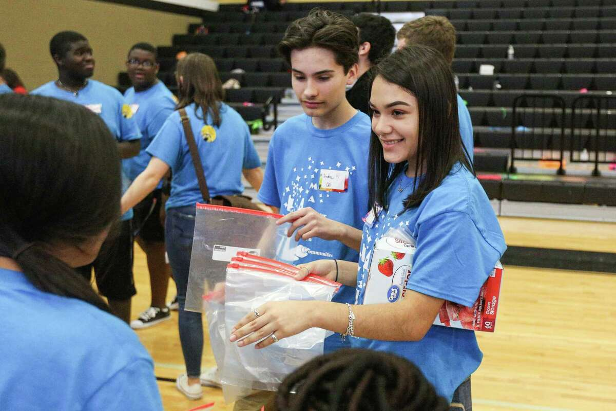 Conroe High School freshmen Britney Torres, left, and Andrew Hartwell, right, hands out plastic bags for care packages for people rescued from human trafficking or homeless during a community service project on Friday, Feb. 16, 2018, at the Conroe High School 9th Grade Campus.