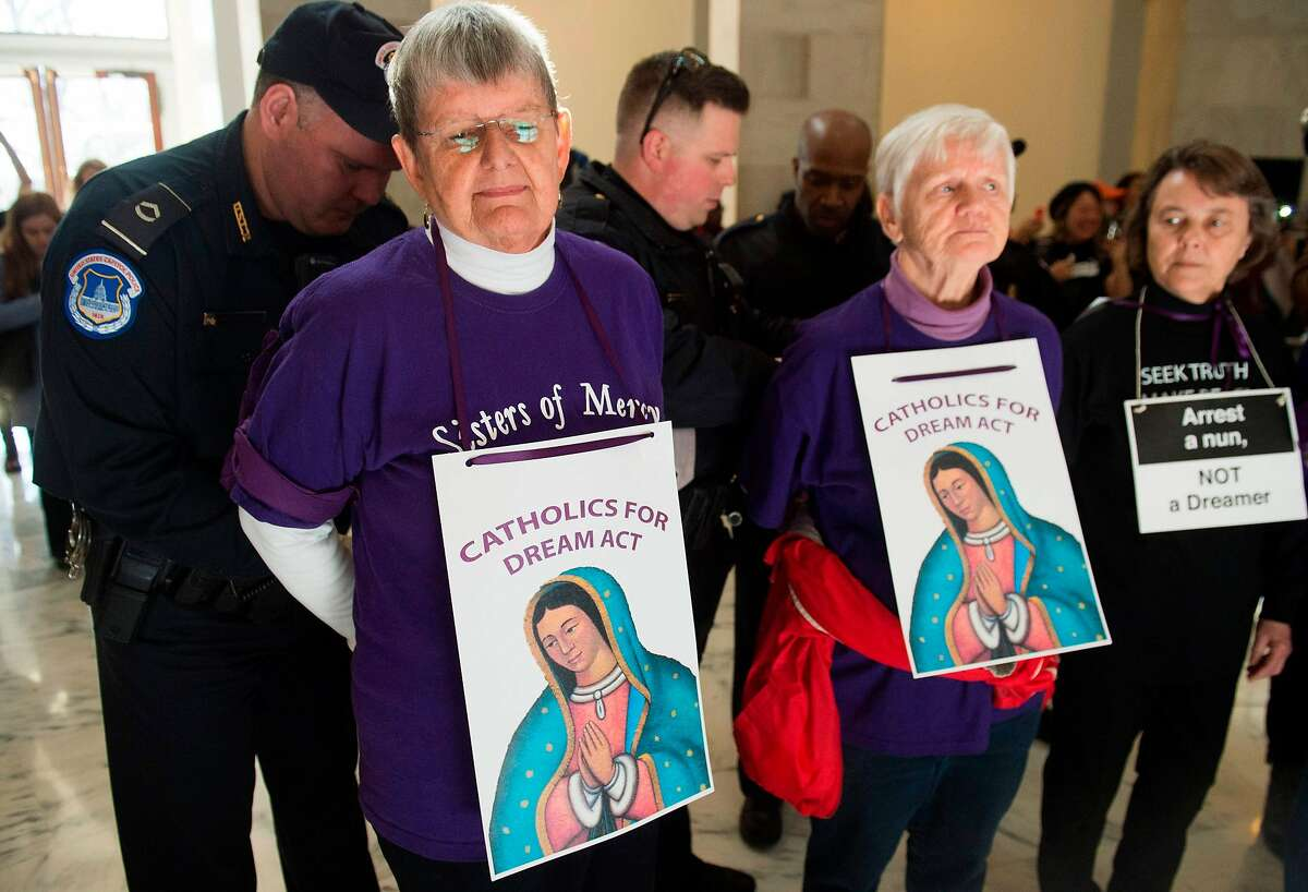 US Capitol Police arrest members of the Catholic community and supporters of DACA recipients, during a protest demonstration in support of the DREAM Act as a part of a Catholic Day of Action with Dreamers, in the Russell Senate Office Building on Capitol Hill in Washington, DC, February 27, 2018. / AFP PHOTO / SAUL LOEBSAUL LOEB/AFP/Getty Images