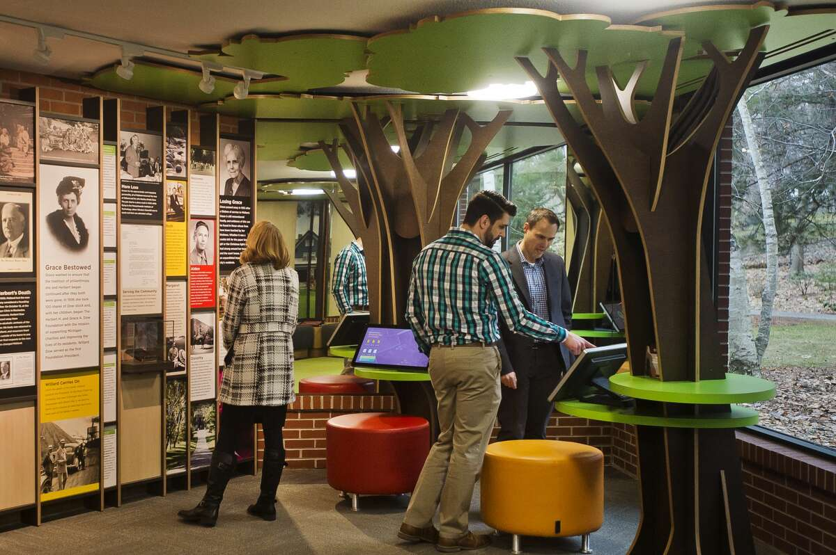 People check out a new history exhibit inside the visitor center at Dow Gardens during a ribbon cutting event on Thursday, March 1, 2018. The event marked the end of a three-year renovation project at the visitor center. (Katy Kildee/kkildee@mdn.net)
