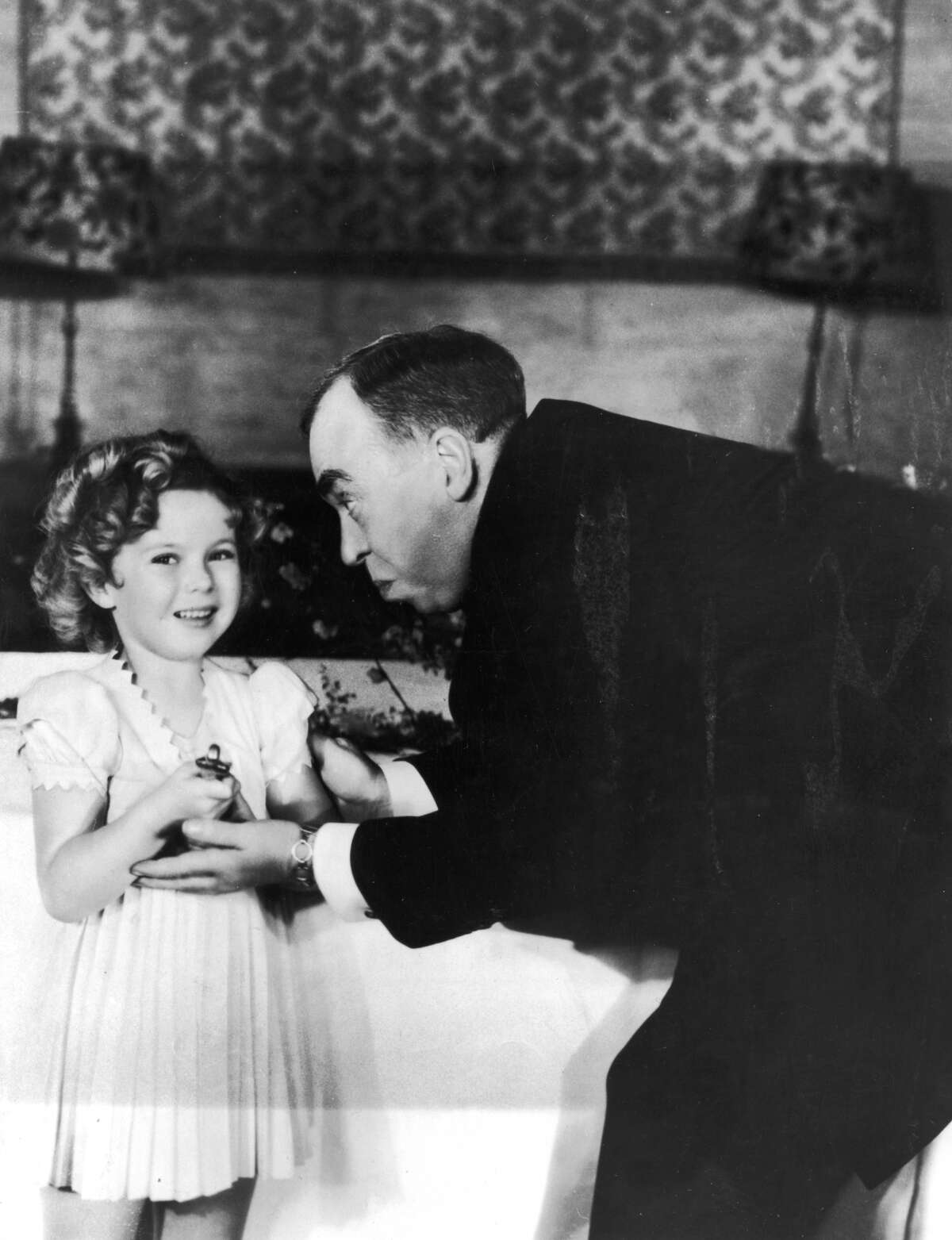 American child actor Shirley Temple receives a special Oscar from American screenwriter Irwin S Cobb at the Academy Awards ceremony in 1934, Biltmore Bowl, Biltmore Hotel, Los Angeles, California.