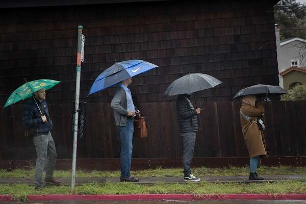 People wait for the bus in the rain on Thursday, March 1, 2018 in Piedmont, Calif.