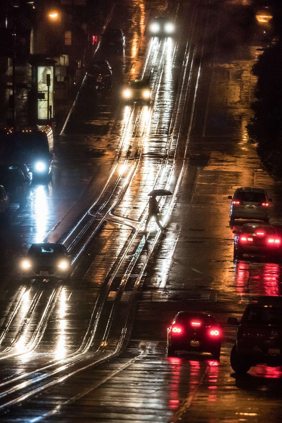 A pedestrian crosses at California and Montgomery streets in the rain. This year's biggest storm to date remains the Jan. 8 deluge that poured 3.15 inches of rain onto downtown San Francisco, officials said.
