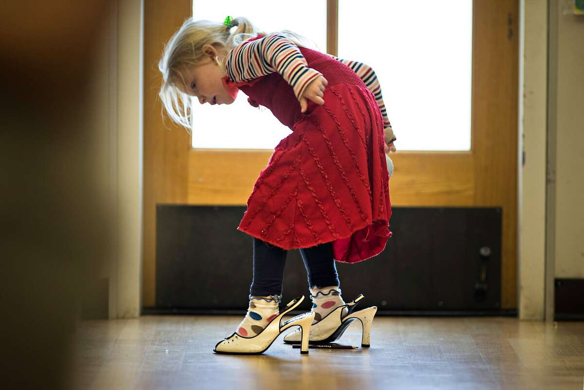 Sadie Scarlett, 5, tries walking in high heels at the Holy Family Day Home on Tuesday, Feb. 27, 2018 in San Francisco, CA. If the child care ballot measure passes, it would help families pay tuition at centers like this one.
