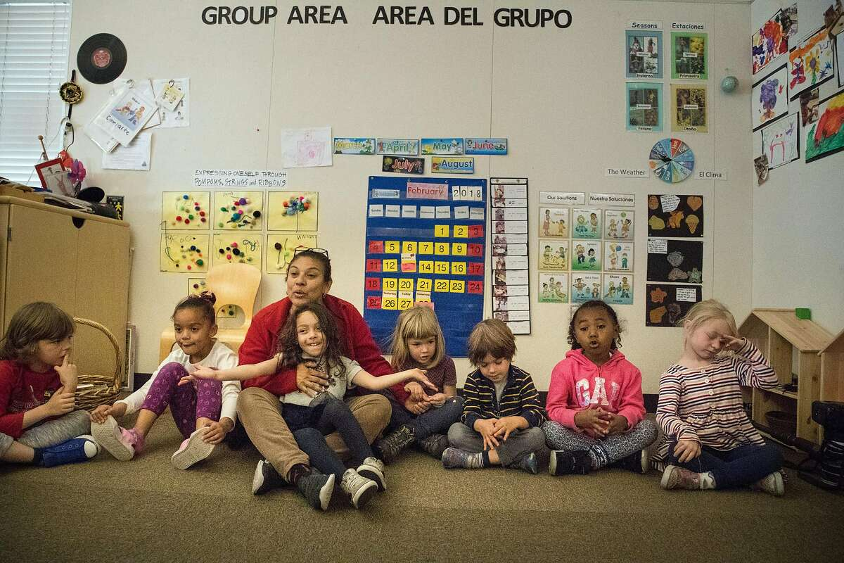Five-year-olds, Elisa Gibson, Jazlynn Padilla, Nova Lucas, Griffin Ells-Kingsbury, Layla Landry and Sadie Scarlett in a circle play with teacher Betty Lopez at the Holy Family Day Home on Tuesday, Feb. 27, 2018 in San Francisco, CA. If the child care ballot measure passes, it would help families pay tuition at centers like this one.
