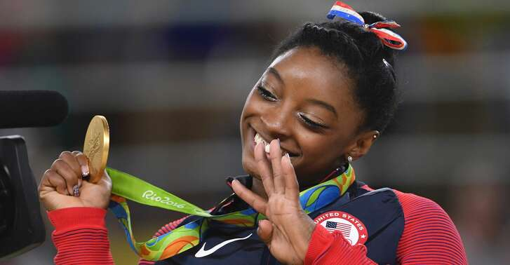 US gymnast Simone Biles celebrates on the podium of the women's floor event final of the Artistic Gymnastics at the Olympic Arena during the Rio 2016 Olympic Games in Rio de Janeiro on August 16, 2016. / AFP PHOTO / Toshifumi KITAMURATOSHIFUMI KITAMURA/AFP/Getty Images
