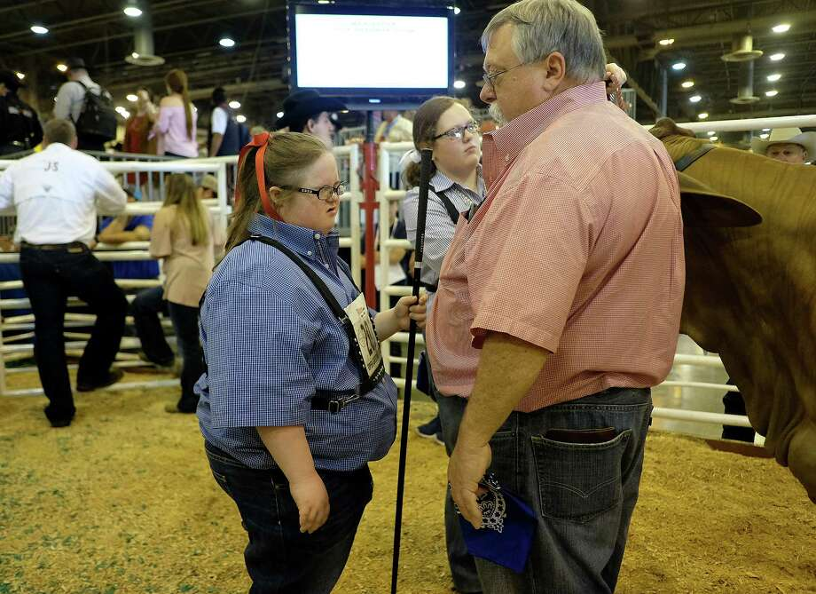 Fourteen-year-old Megan Lambert , shown here with her father Richard, has Down Syndrome, a genetic disorder that causes developmental and intellectual delays. Megan, who is participating in the Houston rodeo, raises and shows animals. Photo: Elizabeth Conley, Houston Chronicle / © 2018 Houston Chronicle