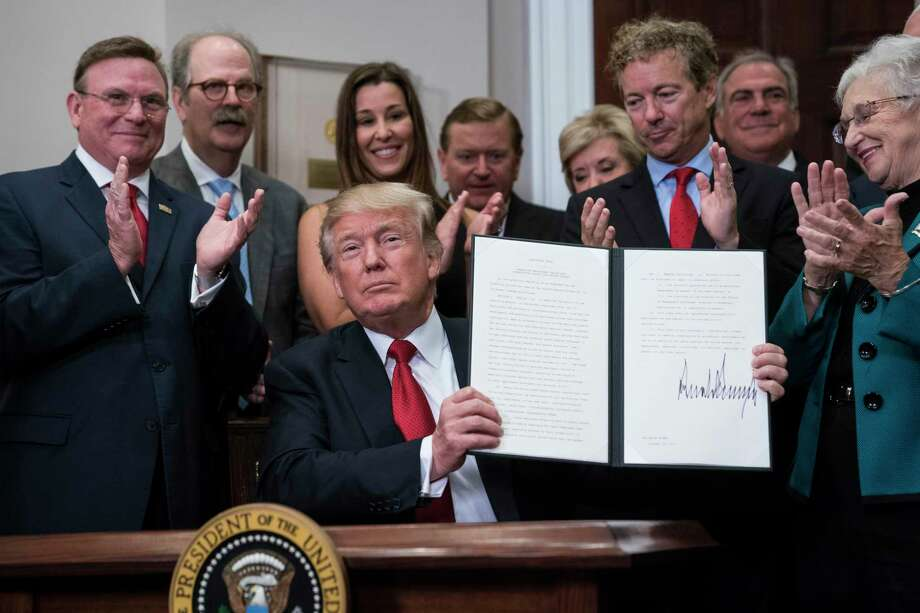 President Donald Trump signs an executive order on health care in 2017. The administration has brought back the individual mandate for health insurance, but only for immigrants. Photo: Jabin Botsford /The Washington Post / The Washington Post