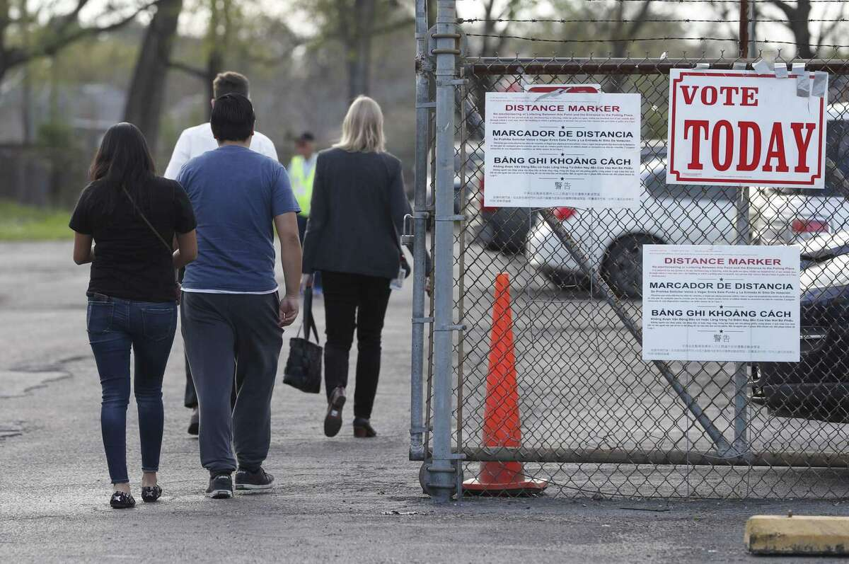 Voters walk past a sign that reads
