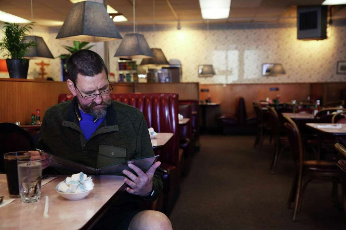 Brendon Ressler checks out the menu during lunch at Vera's Restaurant in Ballard. The restaurant opened in the mid-1960s and hasn't changed much since. They offer typical diner fare, omelettes, burgers and the likes. Photographed, Thursday, March 1, 2018.