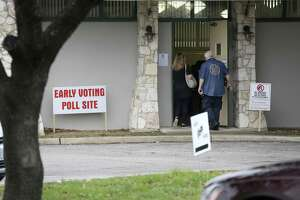 An election judge holds the door for a voter as they enter the early voting site Tuesday, Jan. 20, 2018 at the Lions Field Adult and Senior Center on the first day of early voting for the March 6 joint primary elections. Early voting happens every day through Friday, March 2 at 38 Bexar County locations.