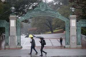 Pedestrians walk past Sather Gate at UC Berkeley in light rain on Saturday, Jan. 16, 2016. Another major rainstorm is due to soak the Bay Area tomorrow.