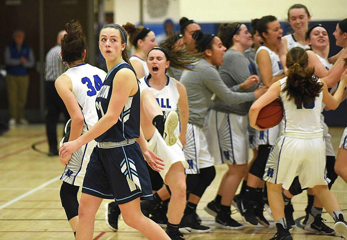 Elizabeth Breslin, front left, of Wilton takes one last look at the scoreboard as Hall celebrates its 52-47 win in the second round of the CIAC Class LL state tournament on Thursday night in West Hartford.