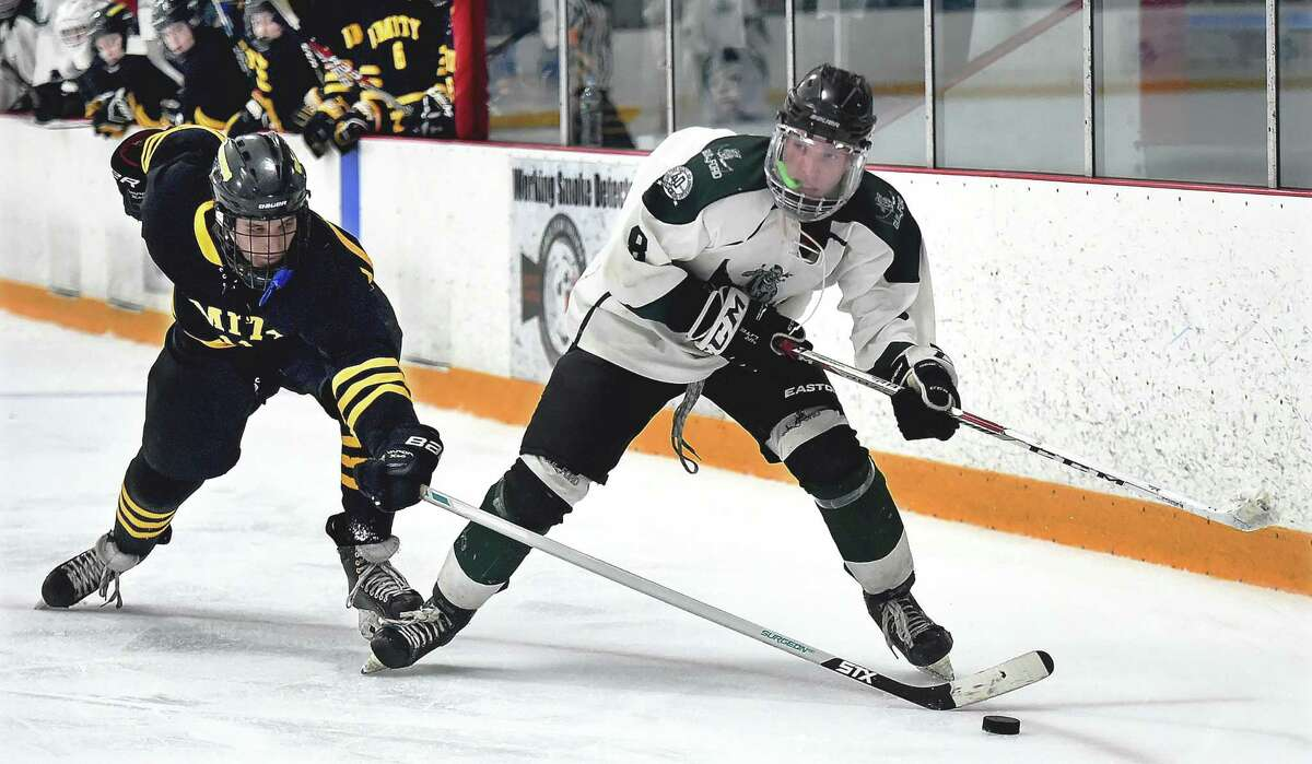 Guilford junior forward Jack Ring looks for an open teammate as Amity senior forward attempts to steal the puck, Thursday, March 1, 28, 2018, in the SCC/SWC Division II hockey semifinal game at Bennett Rink in West Haven. Guilford won, 6-3, and advances to the championship game, Saturday, March 3, 2018 at 4 p.m. at Bennett Rink in West Haven.