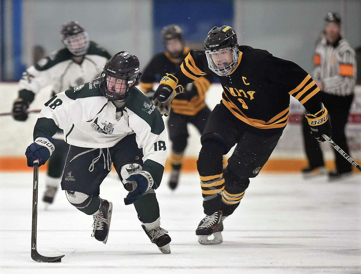 Guilford freshman forward Zach Woxland advances the puck as Amity senior defenseman Michael Miller defends, Thursday, March 1, 28, 2018, in the SCC Division II hockey semifinal game at Bennett Rink in West Haven. Guilford won, 6-3 and advances to the championship game on Saturday, March 3, 2018 at 4 p.m. at Bennett Rink in West Haven.