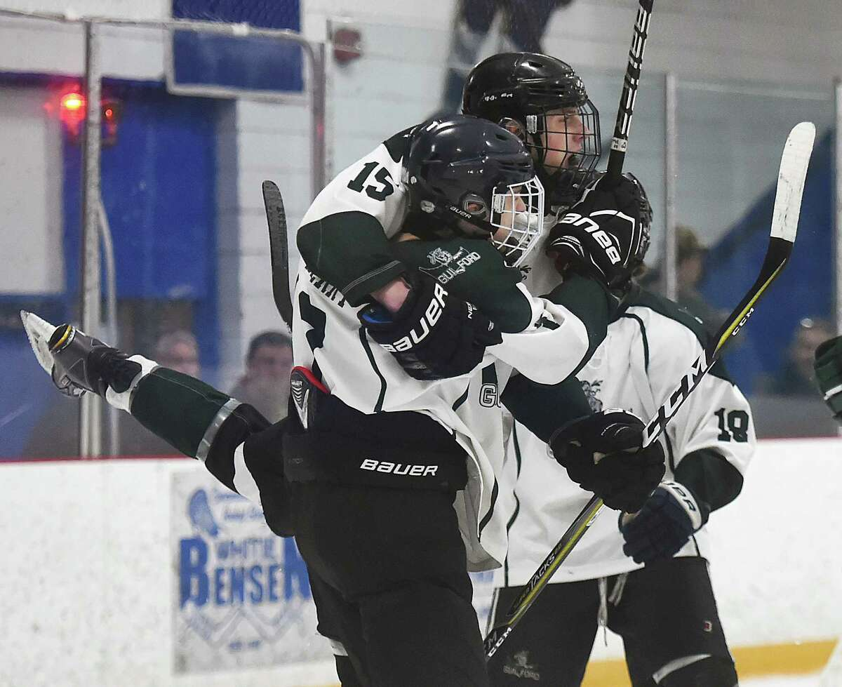 Guilford's Zach Sperry (7), Jake Watrous (15) and Zach Woxland (18) celebrate after Watrous put the first goal on the board against Amity, Thursday, March 1, 28, 2018, in the SCC Division II hockey semifinal game at Bennett Rink in West Haven. Guilford won, 6-3 and advances to the championship game on Saturday, March 3, 2018, at 4 p.m. at Bennett Rink in West Haven.