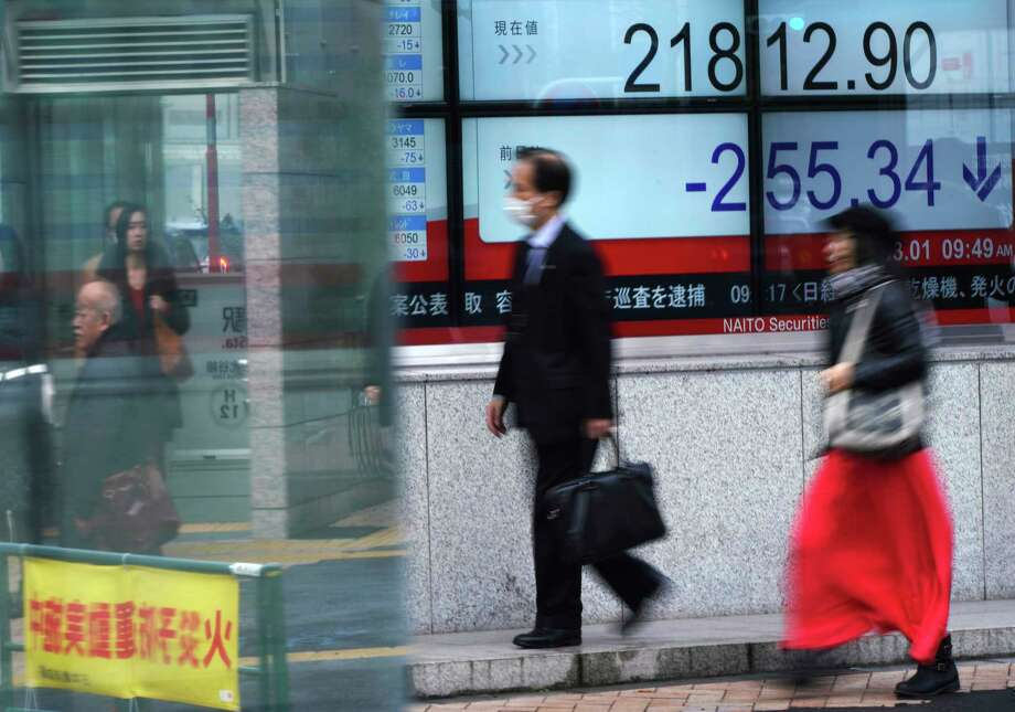 People walk past an electronic stock board showing Japan's Nikkei 225 index at a securities firm in Tokyo, Thursday, March 1, 2018.  Asian shares were mostly lower Thursday as sentiments got dragged down by a slide on Wall Street. (AP Photo/Eugene Hoshiko) Photo: Eugene Hoshiko / Copyright 2018 The Associated Press. All rights reserved.