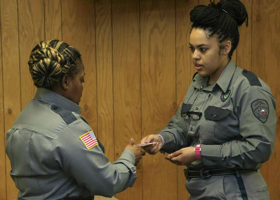 Minnie R. Houston Training Academy Sgt. Stephanie Rhodes, left, and Texas Department of Criminal Justice cadet Shanna Brown, 26, demonstrate the proper steps to check an inmate's ID during a class on Tuesday, Feb. 20, 2018, in Huntsville. Brown started TDCJ as a correctional officer when she was 18 but later left to raise her family about three years ago, and now she is coming back to the program for the second time. ( Yi-Chin Lee / Houston Chronicle ) Photo: YCL / YCL / Houston Chronicle / © 2018 Houston Chronicle