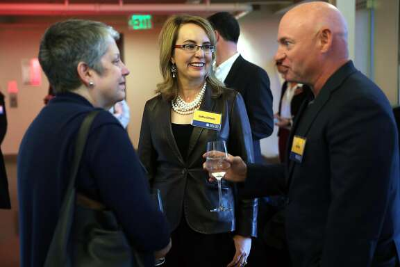 Former US Rep.Gabrielle Giffords and her husband Mark Kelly chat with University of California President Janet Napolitano during a fundraiser for the Gabriel Zimmerman Memorial Scholarship fund in San Francisco, Calif., on Thursday, March 1, 2018.