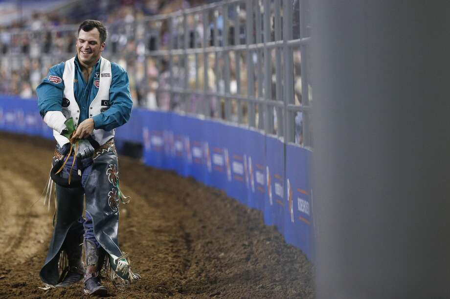 Bareback rider Richie Champion, left, who is from The Woodlands, smiles after his ride on Lil Bucker during Round 3 of Super Series I at the Houston Livestock Show and Rodeo Thursday, March 1, 2018 in Houston. (Michael Ciaglo / Houston Chronicle) Photo: Michael Ciaglo/Houston Chronicle