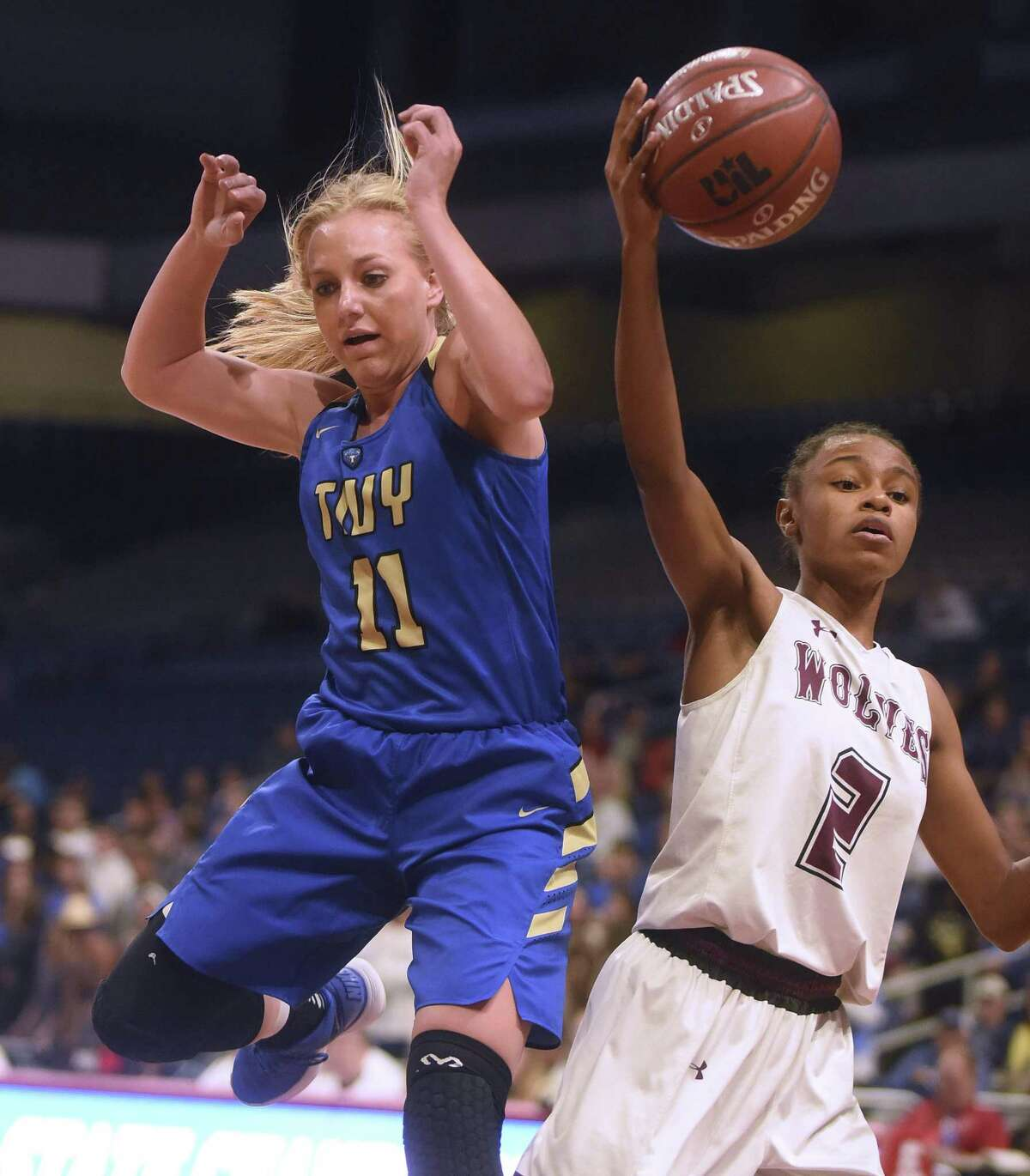 Charli Becker of Kerrville Tivy (11) and Destiny Jackson of Mansfield Timberview fight for a loose ball during UIL Class 5A girls state semifinal high school action in the Alamodome on March 1, 2018.