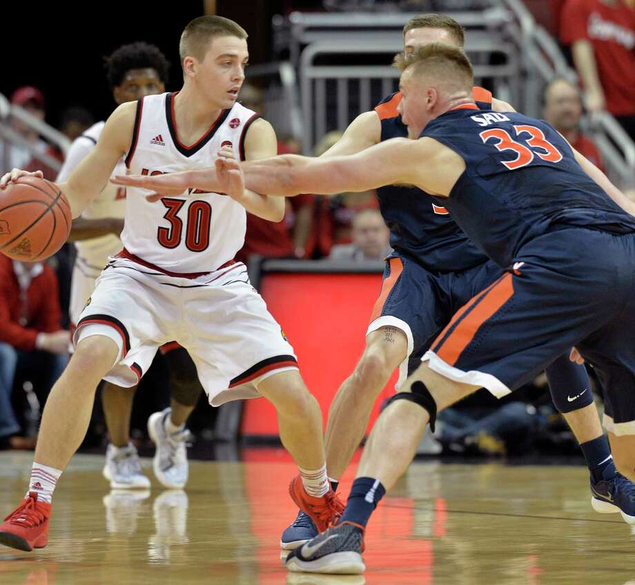 Virginia center Jack Salt (33) attempts to get the ball away from Louisville guard Ryan McMahon (30) during the first half of an NCAA college basketball game, Thursday, March 1, 2018, in Louisville, Ky. (AP Photo/Timothy D. Easley) Photo: Timothy D. Easley / FR43398 AP