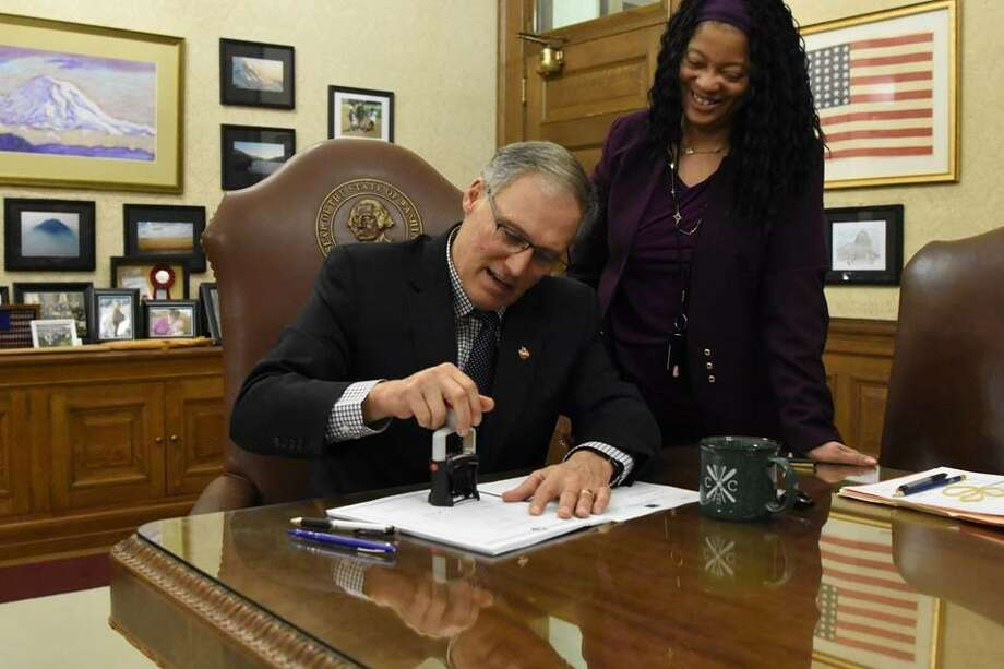 Gov. Jay Inslee stamps his veto to make it official as an aide looks on. Photo: Gov. Inslee's Office