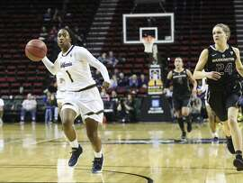 "Cal junior Asha Thomas takes the ball into the key. The 5' 4"" guard sparked the Bears' offense with 22 points."
