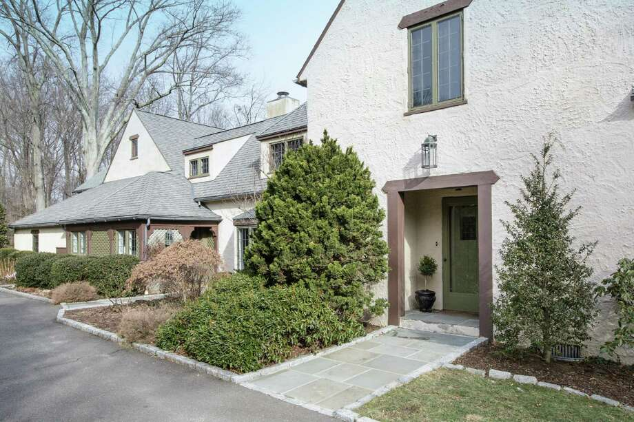 The beige stone and stucco colonial house at 11 Meadowbrook Road offers a perfect mix of charm and lifestyle. Its 2.2-acre level property borders Cherry Lawn Park. / Michael W Smith