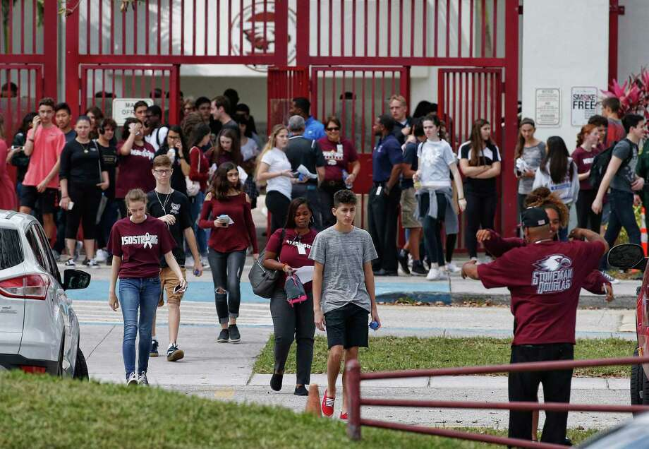Marjory Stoneman Douglas High School students, staff and teachers exit the building following their return to school in Parkland, Fla., on Wednesday. A former student, Nikolas Cruz, opened fire at Marjory Stoneman Douglas High School leaving 17 people dead and 15 injured on Feb. 14. Photo: Rhona Wise / AFP /Getty Images / AFP or licensors