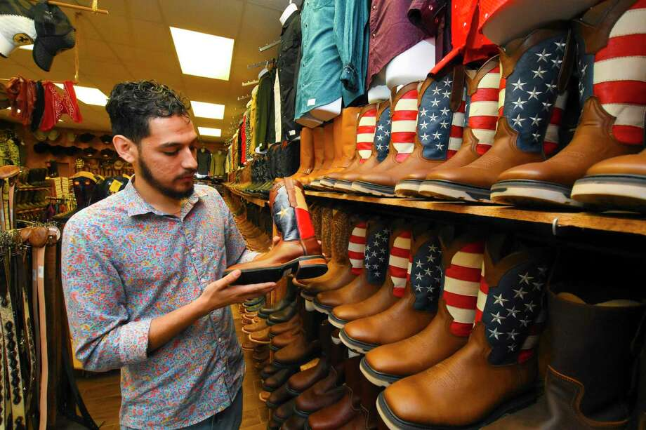 Sergio Ramirez, 23, co-owns Lagarto Boots Western Wear with his mother, Laura Perez, and younger sister, Laila Ramirez. The store holds roughly 800 pairs of boots Photo: Tony Gaines/ HCN, Staff / Houston Chronicle