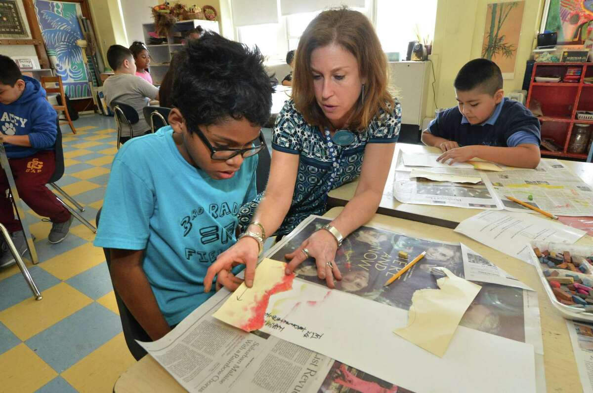 Art teacher Rhonda Siletto works with Miguel Castellanos on his Asian landscape panel where students in her third-grade Tracey Elementary School class learn to use different media to create a scene with all the elements in the style of Asian artists on Wednesday Feb. 21 in Norwalk.