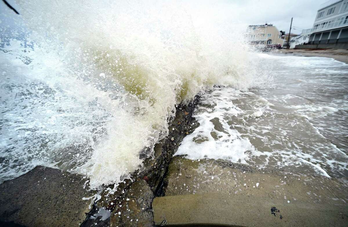 Waves crash onto Laurel Ave. in the Wildemere Beach section of Milford during high tide on March 2, 2018.