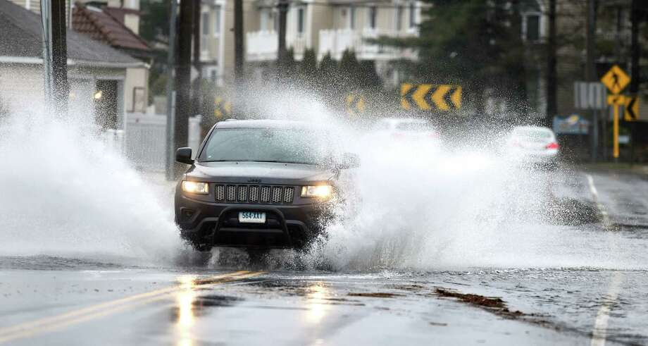 Cars travel through a flooded Merwin Ave. in Milford on March 2, 2018. Photo: Arnold Gold, Hearst Connecticut Media / New Haven Register