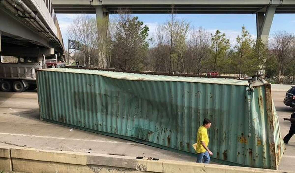 A container sits in the eastbound lanes of Interstate 10 after it struck the Houston Avenue bridge on Friday, March 2, 2018, in Houston. The truck hauling it was using a flatbed trailer, which made the container have a total height of more than 14 feet, officials said.